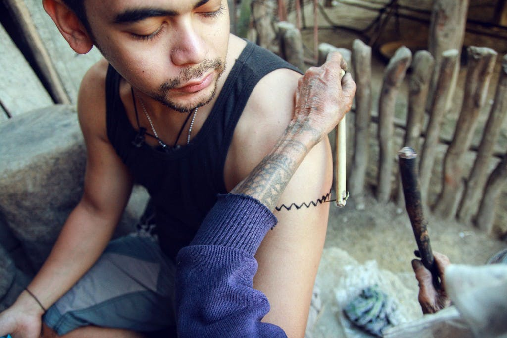Backpack traveler Julian Rodriguez getting a traditional tattoo in Buscalan