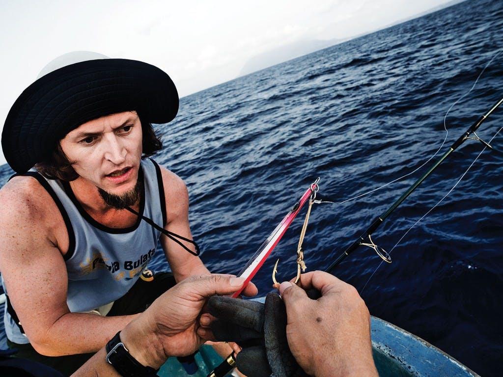 Gordon Uy teaches Chip Childers the basics of fishing. Photo by Ferdz Decena