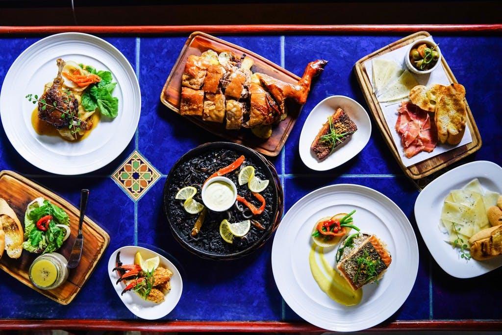Dos Mestizos Tapas & Bar's lavish spread, which includes squid ink paella and cochinillo